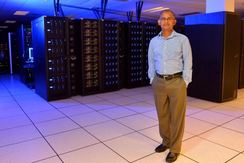 Professor Arun Somani stands next to an ISU computer that could fill a garage