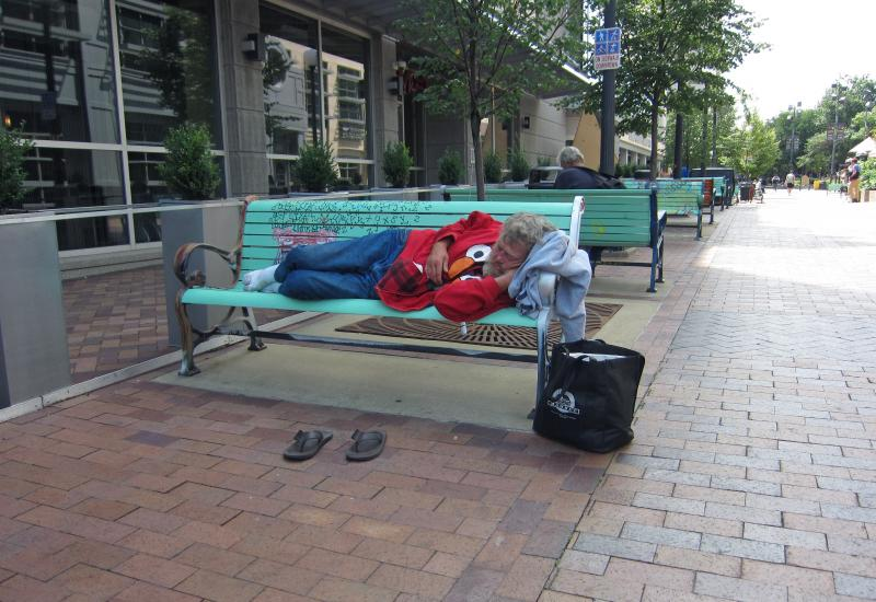 A man sleeps on a bench in Downtown Iowa City on July 31, 2013. Sleeping on benches between the hours of 5 a.m. and 10 p.m. would violate an ordinance the city council is considering and could result in a $65 fine.