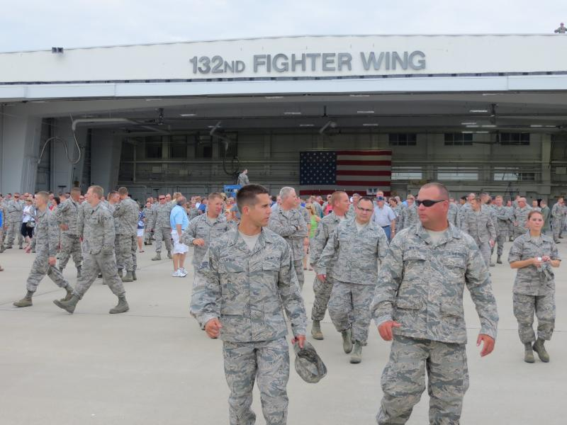 Iowa Air Guard members emerge from hanger to watch the final flyover