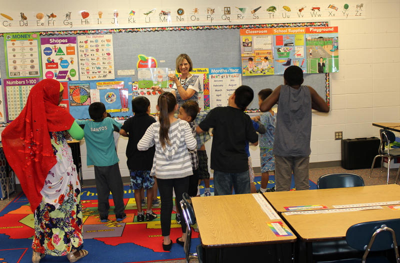 "Teacher Kay Thompson leads her ""newcomer"" class at Florence Wilson Elementary School in reading ""If You're Happy and You Know It."""