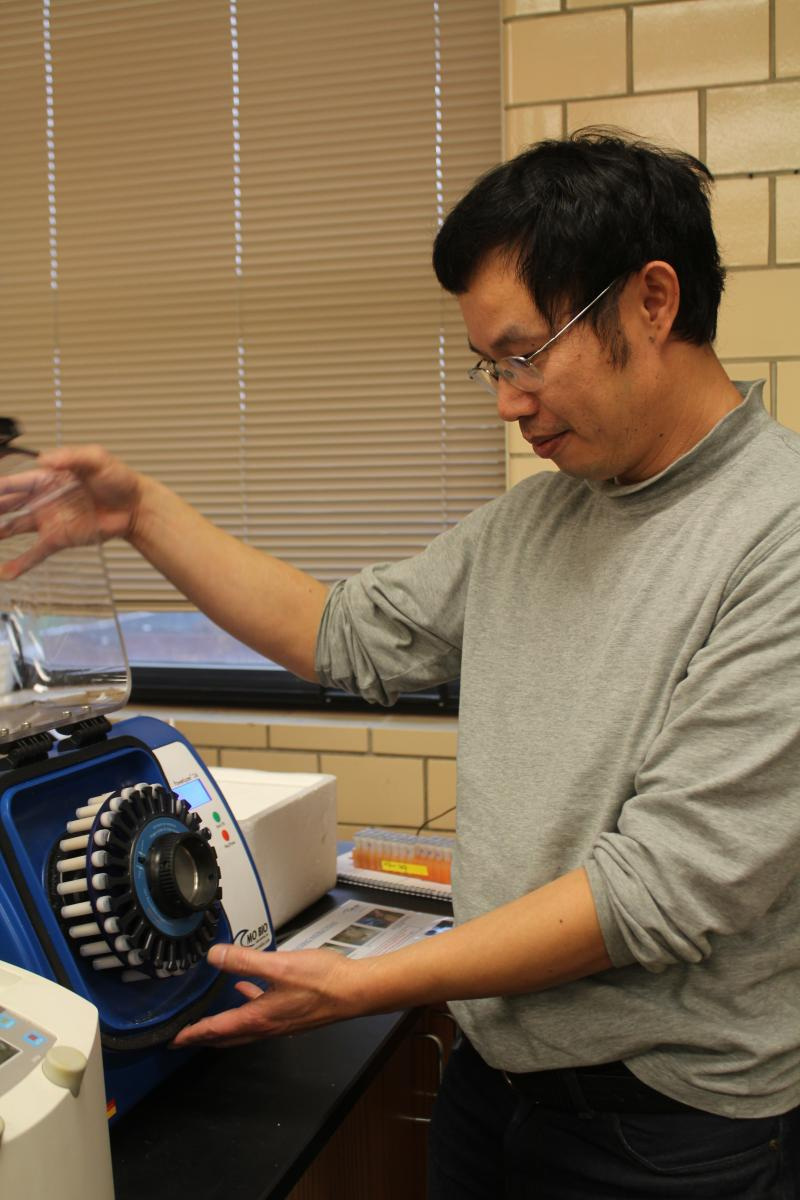 Iowa State associate scientist Chiliang Chen positions soil samples in a machine called a Powerlyzer that will smash up and homogenize the tissue so biologists can extract the microbial DNA within.