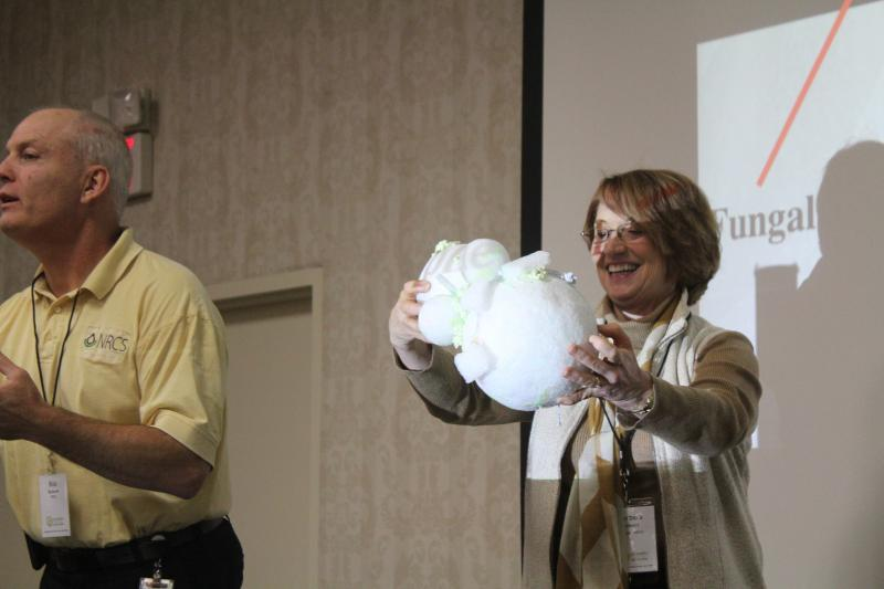 Iowa's state agronomist Barb Stewart holds a collection of foam balls held together by silly string--a model of the relationship between soil and a fungus.
