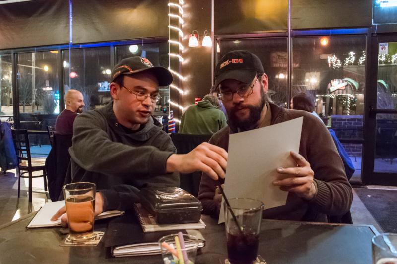"Jonathan and Sean Eike compare sketches during the monthly drink and draw at the bar Goodsons.  This month they published their first comic ""The Night Before Christmas at the Comic Book Shop"", an adaption of the 1823 poem ""The Night Before Christmas""."