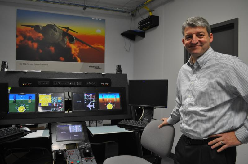 Colin Mahoney of Rockwell Collins stands next to a flight deck that will be installed in transport jets for the Brazilian Air Force.