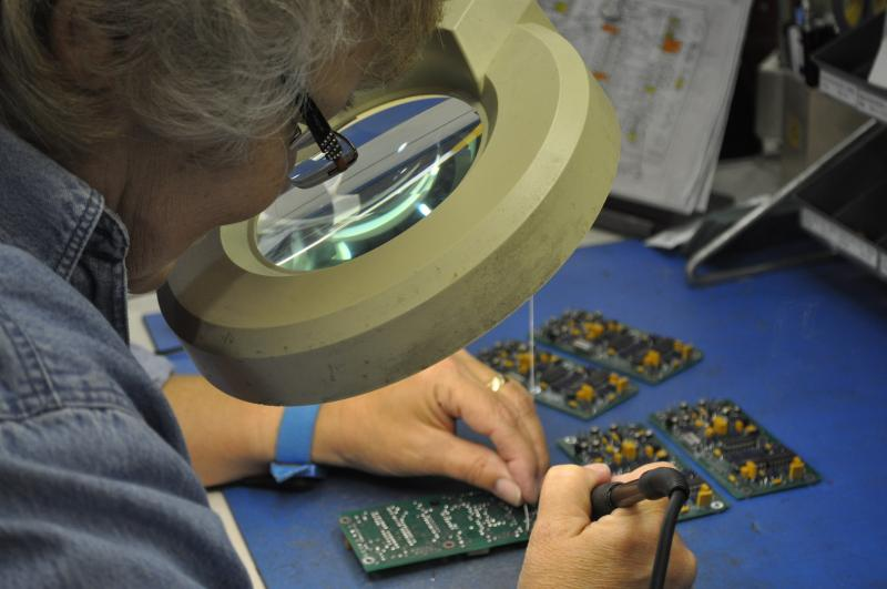 Technician Chrys Strauss works on a circuit board in the J-Tec lab.