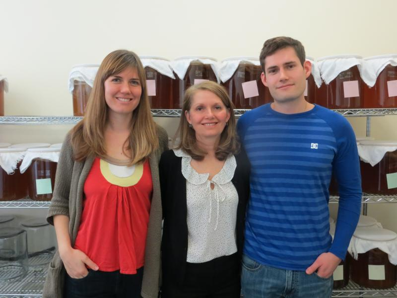 Meghan, Debi, and Jack Dowd stand in front of fresh batches of fermenting kombucha.