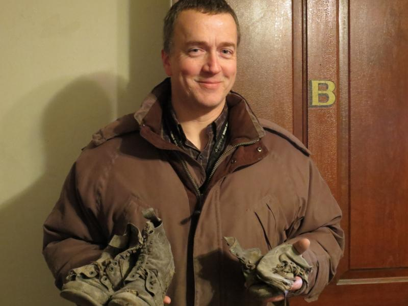Greg Young stands with two pairs of 1930's shoes he found in a crawl space of the Brewer House