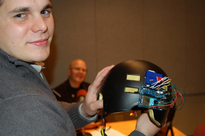 Shawn Cornally holds a student-designed helmet with concussion detection hardware. (host Ben Kieffer in background)