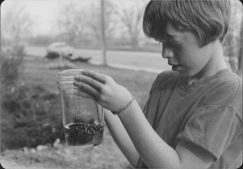 ISU Historian Pamela Riney-Kehrberg's brother Scott looks at a salamander captured in the irrigation ditch where he played as a child.