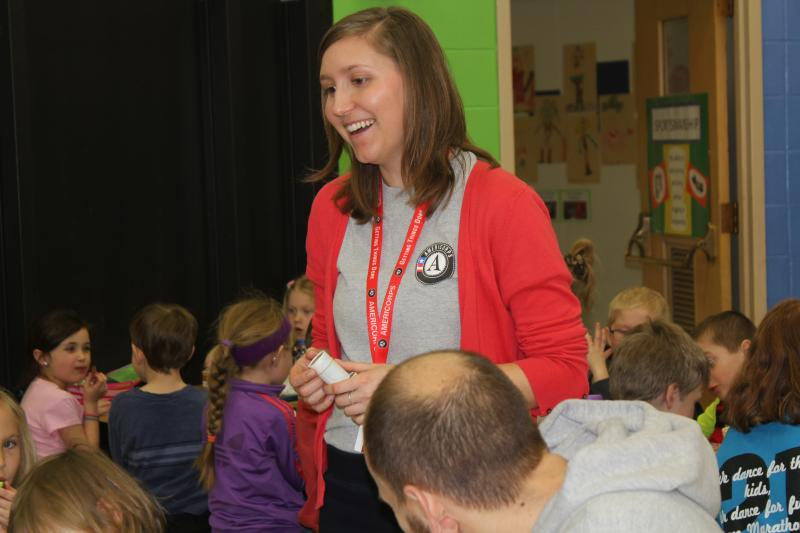 AmeriCorps service member Megan Woodward visits with students at John Cline elementary school in Decorah during their lunch period. She hands out stickers to reward those who try new foods.
