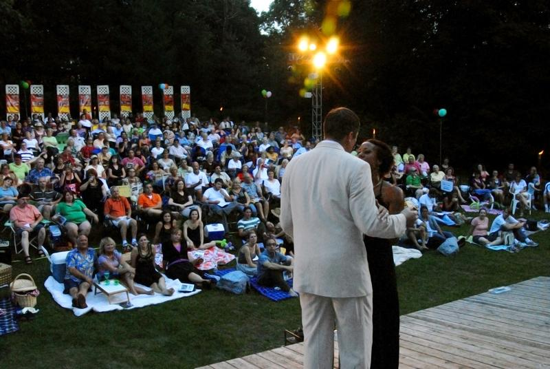 An audience looks onto the stage from the lawn of the historic Brucemore Mansion in Cedar Rapids.