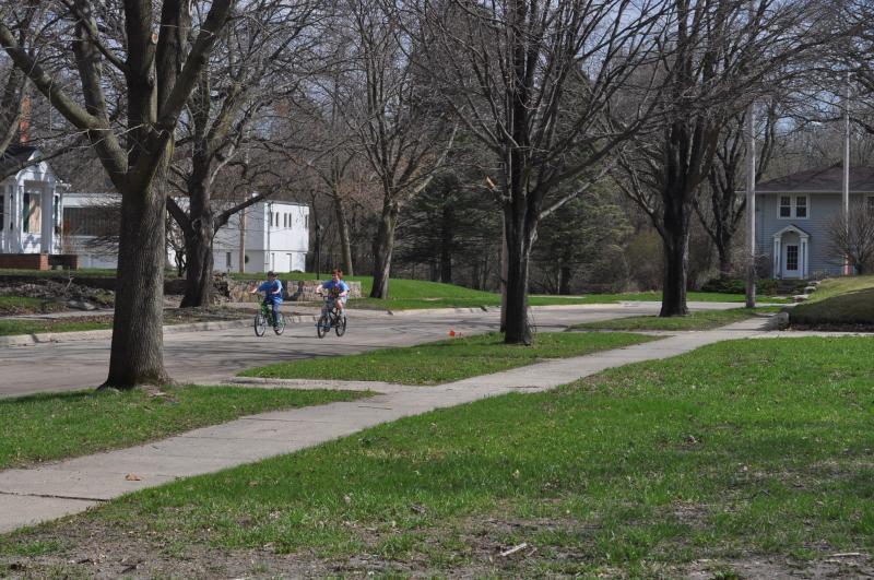 Children ride bicycles in Mason City's East Park neighborhood, where the last of the buyout home still stand.