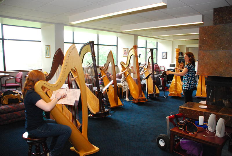 An instructor works with a group of harpists in a workshop at the Five Seasons Chamber Music Festival