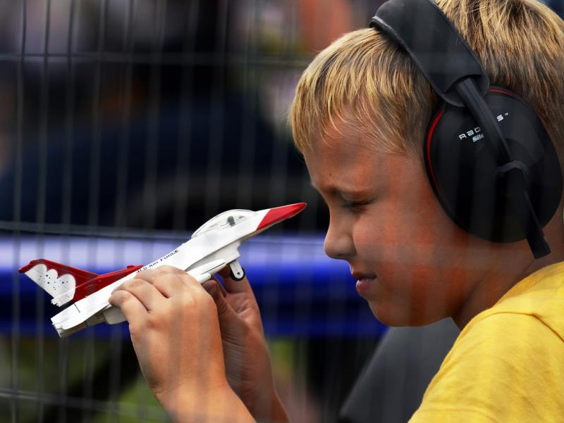 A fan plays with his Thunderbird F-16 souvenir during the Quad City Air show at the Davenport Municipal Airport in Iowa