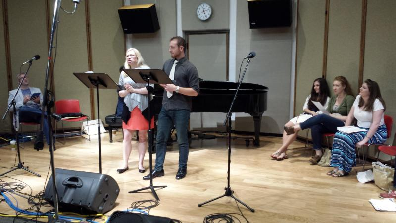"""Mikado"" cast members Lauren Henderson-Turner (Katisha) and Arthur Beutel (Ko-Ko) sing a duet live in Studio One as fellow cast members listen and laugh along."
