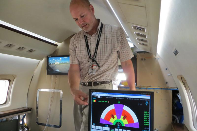 Rockwell Collins Senior Systems Engineer, Gregory Koenigs, explains the advanced radar displays aboard the company's experimental aircraft which is analyzing storm clouds in the flight path.