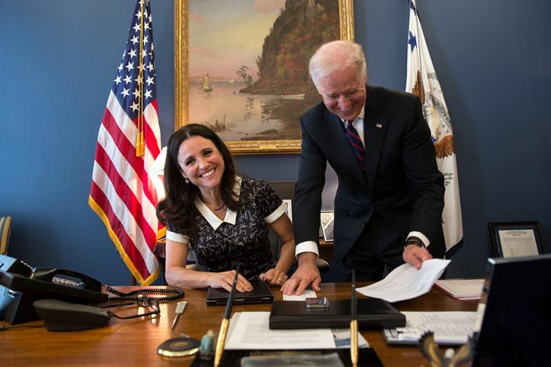 "Vice President Joe Biden jokes with Julia Louis-Dreyfus of the TV show, ""Veep,"" as she sits at his desk in the Vice President's West Wing office at the White House, April 12, 2013"