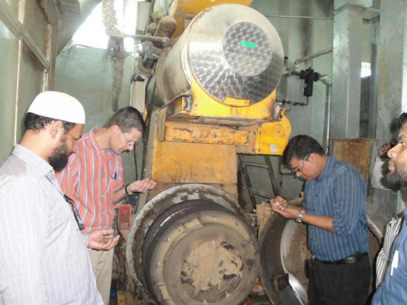 At a feed mill in Bangladesh, Rosentrater and local workers inspect the product.