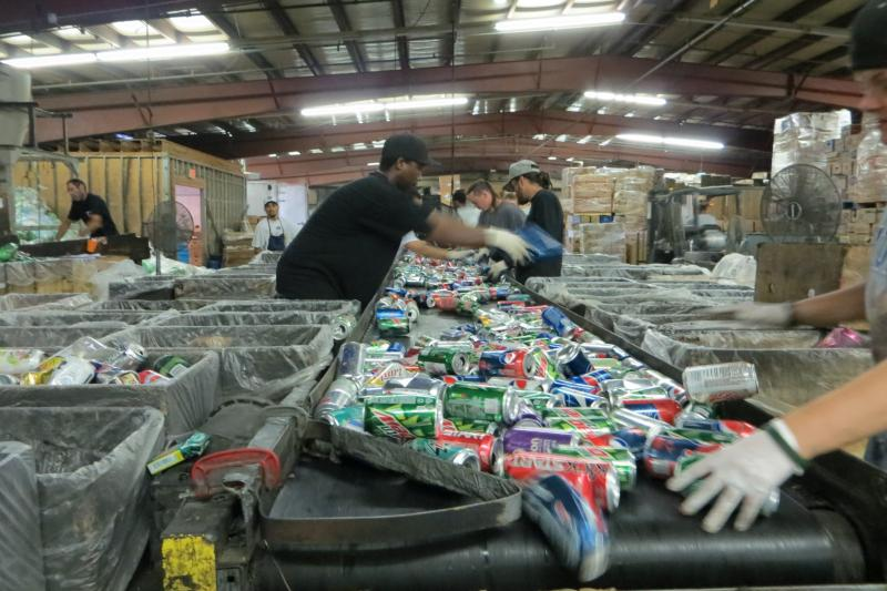 A look down the can line.  Workers grab cans and sort them into boxes by distributor. As the area's largest distributor, Pepsi stays on the line until the end.