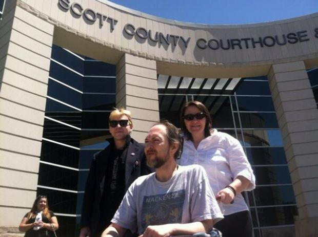 Benton Mackenzie, in a wheelchair, and his wife, Loretta, outside the courthouse Wednesday.