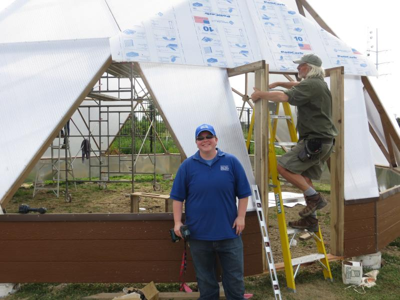 Assistant Shelter Manager A.J. Olson stands outside the dome on Day 2 of construction.
