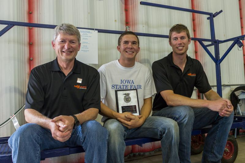 Agtelligent's Doug and Brent Applegate sitting with 18-year-old Paul Queck from Truro at the Ag Mechanics and Technology Show.  Queck is the winner of the Innovation Award for inventing a cart designed to haul cattle show equipment.