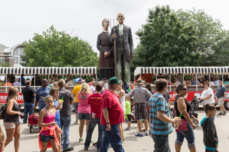 "This 25-foot tall replica of the figures in Grant Wood's ""American Gothic,"" are capturing the attention of fairgoer and amateur photographers."