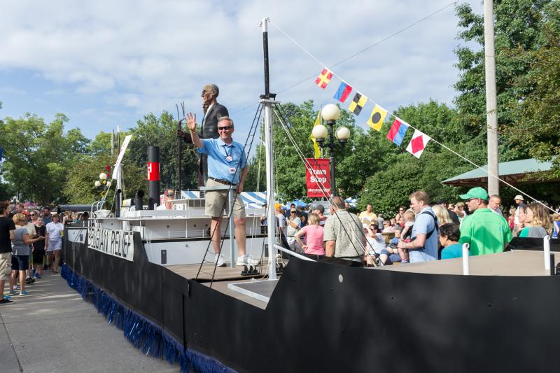 "Jerry Fleagle, Executive Director of the Hoover Foundation rides on a float modeled after a cargo ship that in 1914 delivered food to Belgium. The ""Belgium Relief "" was chaired by Iowa-born businessman Herbert Hoover."