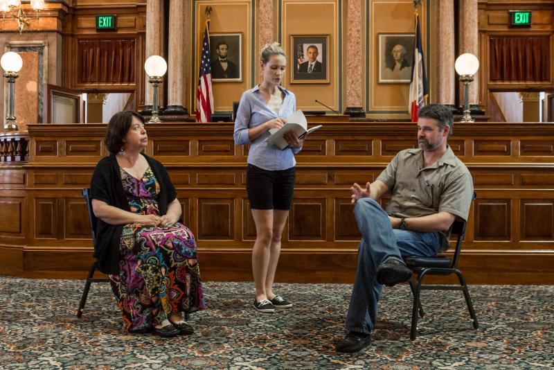"Mary Bricker, Elizabeth Klinge, and Matt McIver respectively playing the roles Mary Lincoln, Eve Harper and Abraham Lincoln during a rehearsal for ""Lincoln's Last Interview"" in the House of Representatives Chamber at the Iowa Capitol."
