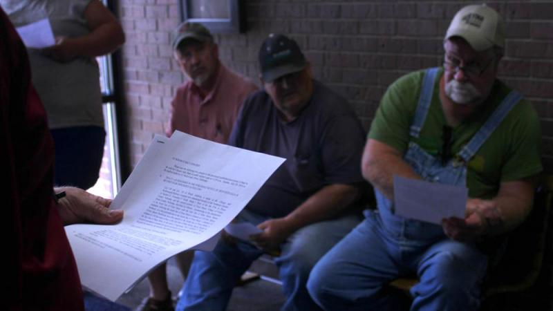Local farmers read the auction paperwork for the Pierce Elevator at the county courthouse. The elevator's failure left farmers with about $9 million in unpaid claims.