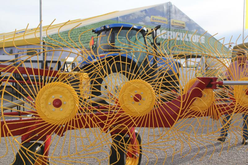 Yellow hay rakes drew attention to the New Holland exhibit at the Farm Progress Show in Boone Tuesday.