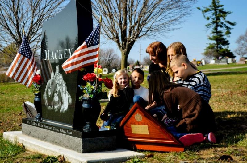 Kaanan Mackey and her five children visit the grave of Matthew Mackey who was killed in an accident while on active duty
