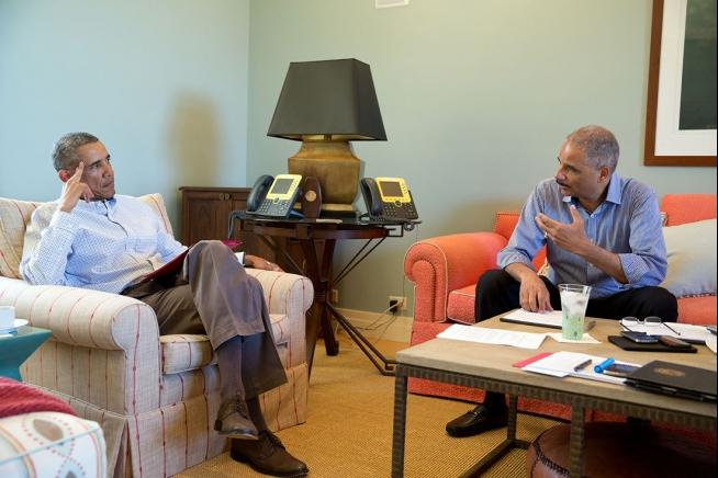 President Barack Obama talks with Attorney General Eric Holder to discuss the situation in Ferguson, Mo.