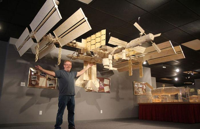 Patrick Acton poses with his matchstick recreation of the International Space Station. Much of Acton's artwork is on display in Gladbrook.