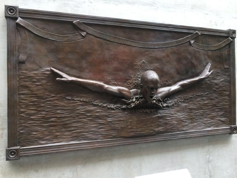 A bronze sculpture at the Campus Recreation and Wellness Center on the University of Iowa Campus. Jack Seig, who developed the dolphin kick, is depicted.