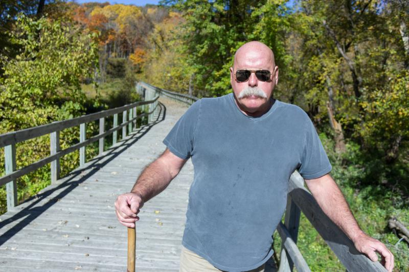 Friends of Effigy Mounds Leader Tim Mason stands on one of the illegally constructed boardwalks at Effigy Mounds National Monument.