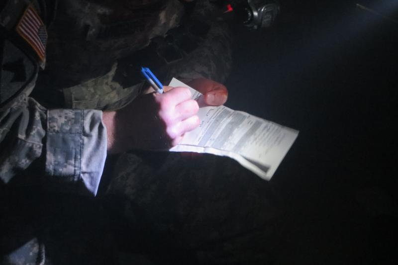 """Medic, with """"blood"""" on his finger, takes notes under battlefield conditions"""