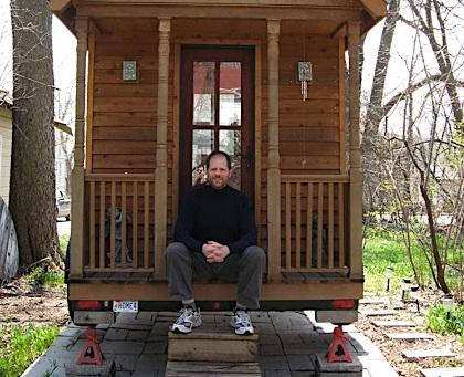 Small House Society President Greg Johnson sits on the porch of his tiny house,