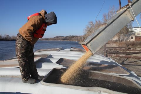 An MFA Agriservices worker monitors the soybean chute as the barge fills up on the Missouri River in Glasgow, Mo.