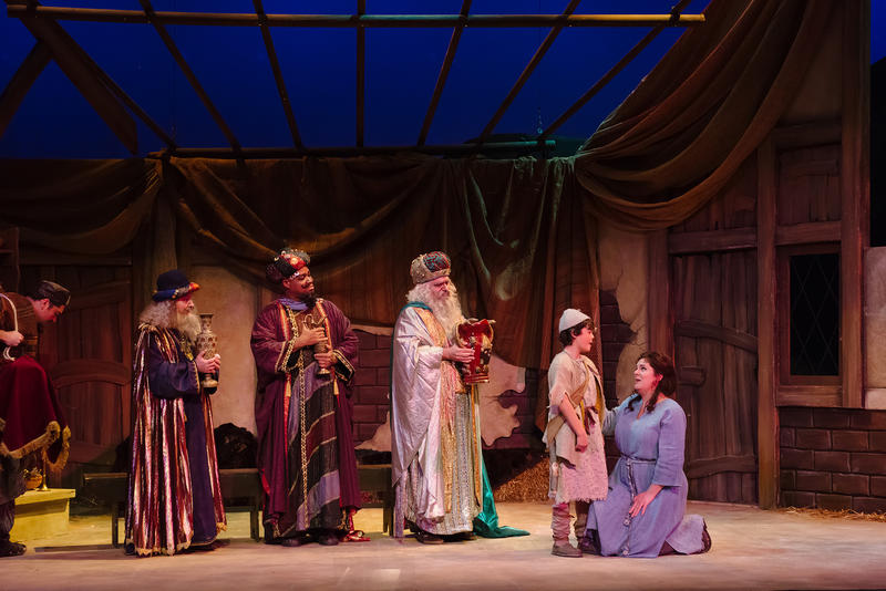 The three wise men watch as Amahl and his mother converse