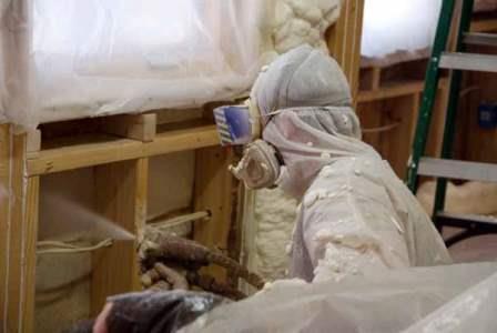 A worker sprays foam insulation in a home
