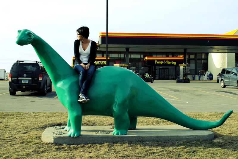 Mercedes Potter sits on a dinosaur at an Iowa gas station.
