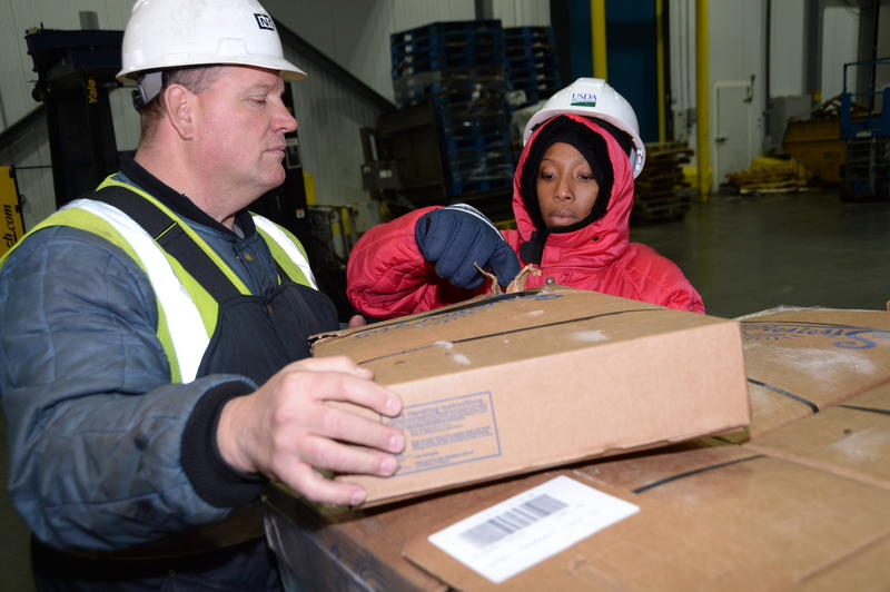 U.S. Department of Agriculture (USDA) Food Safety Inspection Service (FSIS) inspector examines a shipment imported frozen meat at the Port of New Orleans in New Orleans, LA on Thursday, Nov. 21, 2013.
