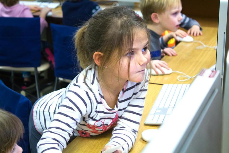 Avery Voss reaches over to help a new kindergartener in her class get started with a computer coding puzzle.