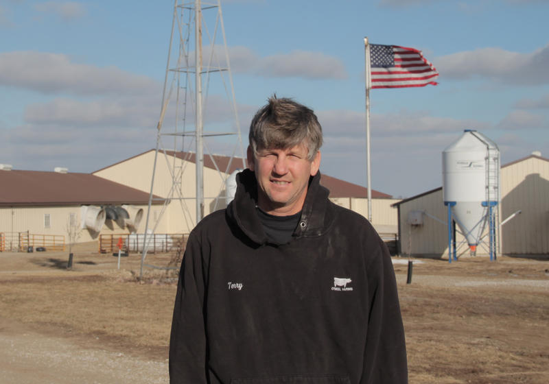 Terry O'Neel stands in front of hog barns on his farm near Friend, Neb. O'Neel is concerned Nebraska could lose one of its pork processing plants if the state's hog industry doesn't keep up with neighboring states.