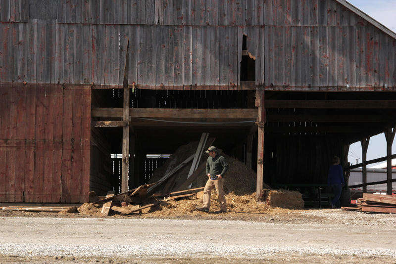 Farmer Levi Greuel spends a sunny Saturday afternoon fixing up his farm equipment and tearing down an old wooden barn in preparation for planting season.