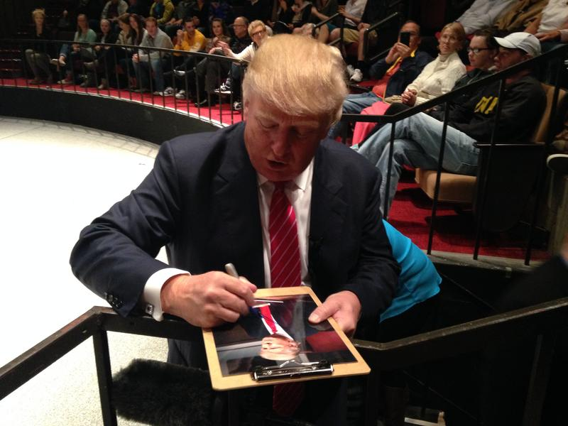 Real estate magnante Donald Trump signs a photo after speaking to students at Simpson College in Indianola. Trump is considering a run for the White House (04/08/2015.)