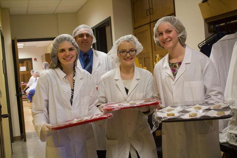 The creators of a vegan, gluten-free hummus and cracker snack bring out samples for the visiting panel of industry professionals. (left to right: Shannon Cihak, Cory Rasmussen, Emily Schmidt, and Nicole Walski)