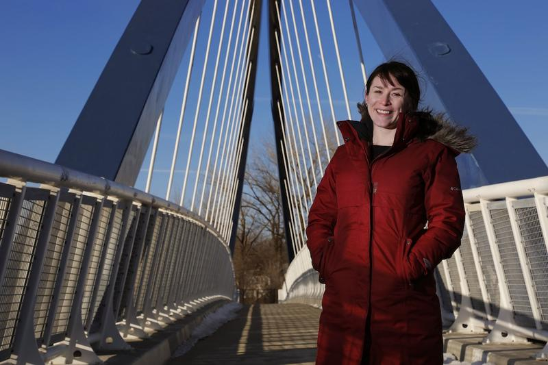 Katy Swalwell, assistant professor in the ISU School of Education, stands on a memorial bridge in Des Moines, named after American civil rights pioneer Edna May Griffin