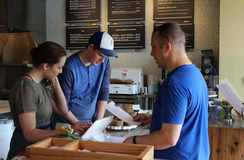 Heirloom Bakery owner Scott Meinke, center, helps a customer choose from their locally sourced menu.
